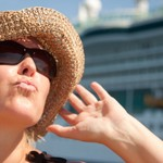 Beautiful Vacationing Woman on Tender Boat with Cruise Ship in the Background.