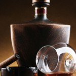 bottle and glass of brandy and cigar on wooden table on brown background