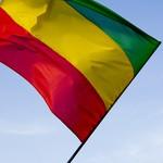 Red, yellow, green reggae flag over blue sky