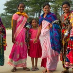 Indian women in brigt traditional sari in the Goa beach